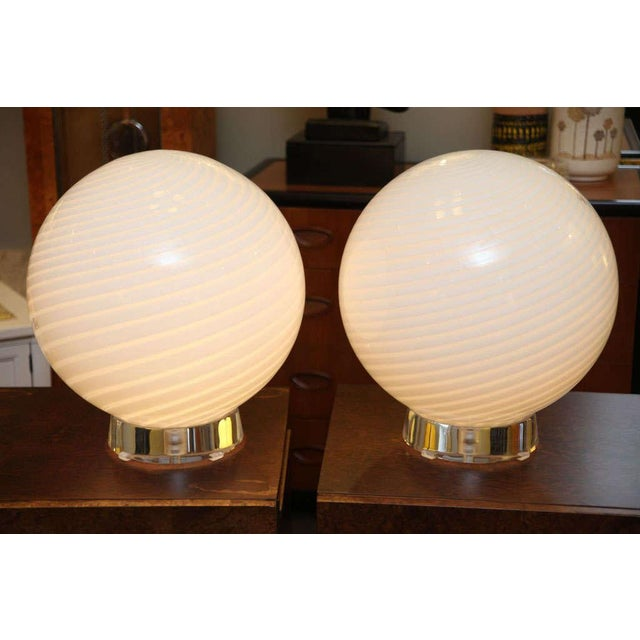 "REDUCED FROM $3,600. Grand scale with this pair of Murano mezza filigrana blown glass orb table lamps on 3"" thick lucite..."