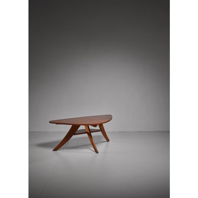 A coffee table signed 'Cool', standing on three ebonized black legs. The table has two triangle shaped tops, one blonde...