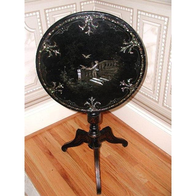 C.1850 Napoleon III black papier mache tilt top table from France is inlaid with mother of pearl in the intricate design...