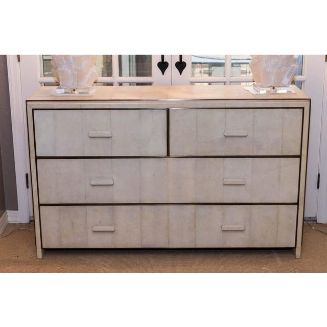 White Shagreen four-drawer commode with bronze trim in excellent condition. This piece is made to order and current...