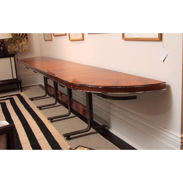Exceptional and very large console with plateau and stretcher in figured rosewood veneers; the curved supports in shaped...