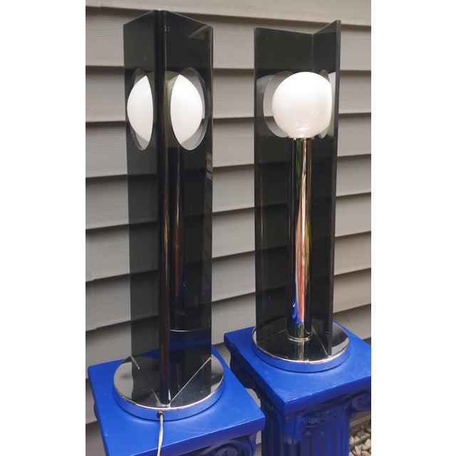Amazing pair of 1970s smoked lucite and chrome table lamps. We love the dramatic angles of the smoked lucite in contrast...