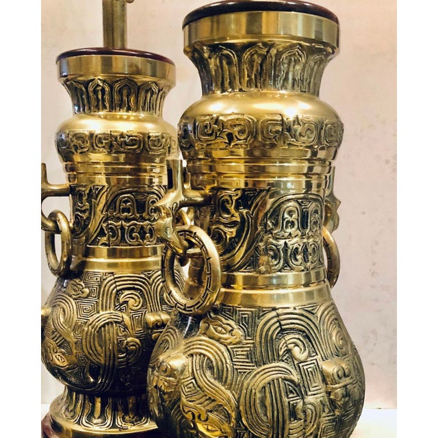 A pair of mid century reticulated brass lamps with side rings. Lamps have matching finials and are on wooden bases,...