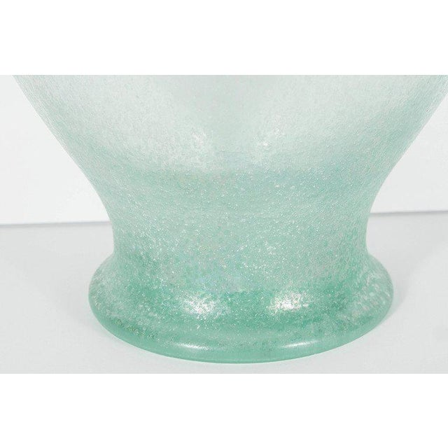 This large hand blown vase /urn features a pale iridescent celadon green glass with a scavo finish.It features a scrolled...