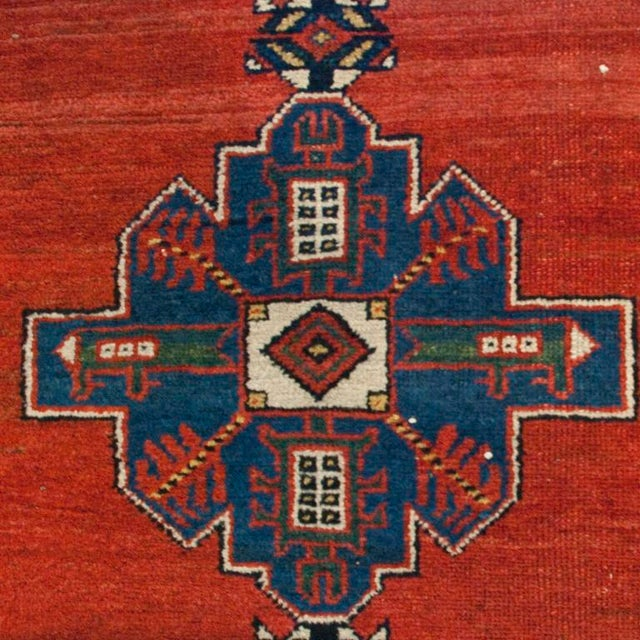 An early 20th century Persian Lori carpet runner with six medallions on a crimson background surrounded by multiple...