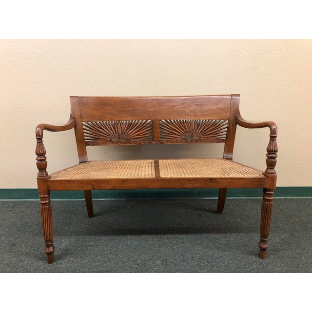 This is a caned bench with fine woodworking. Artisan craftsmanship can be seen in the carved details on the backrest, most...