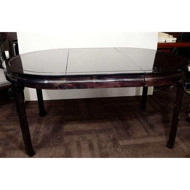 Mid-Century modern dining table in ebonized mahogany. It includes a 20 inch leaf which fits into the center. Mint restored...