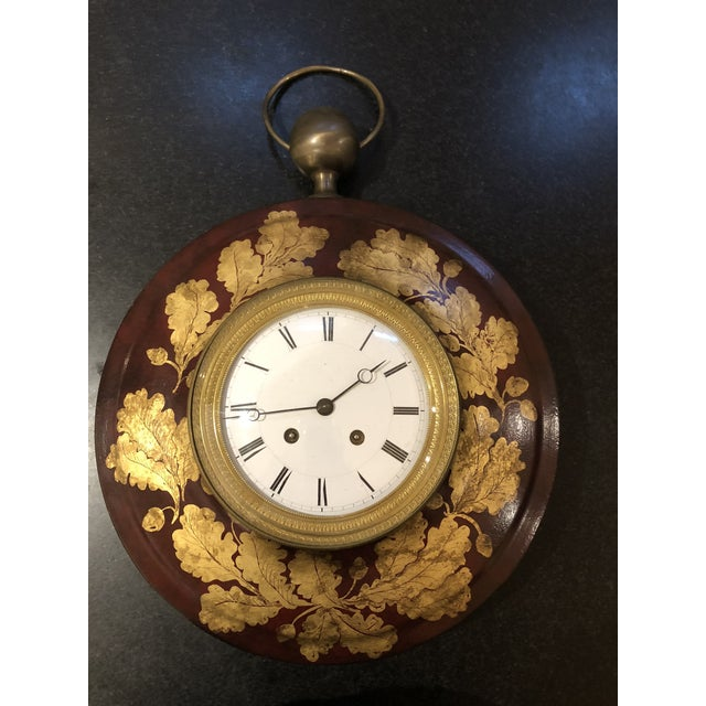 A gorgeous antique garnet tole clock with brushed gold laurel accents. Includes key.