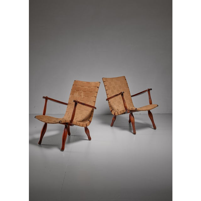 A pair of wooden lounge chairs in the style of Elias Svedberg for Nordiska, with a beige webbed canvas seating. The chairs...