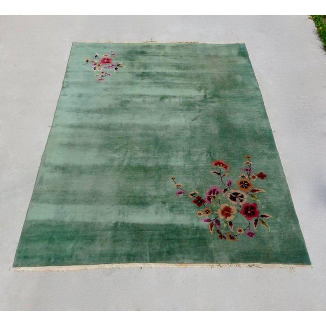 Green field Nichols Art Deco rug with floral decoration on two corners. Slight discoloring on one blank corner shown in...