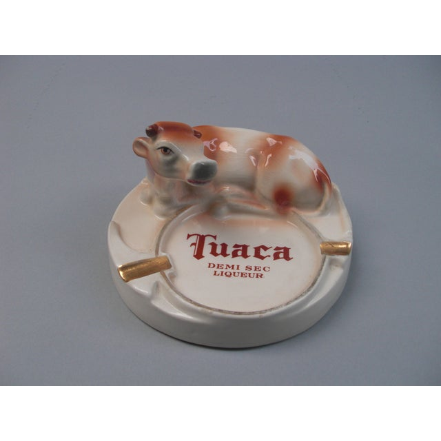 """This vintage, Italian porcelain advertisement ashtray is marked """"Tuaca Demi Sec Liquer"""" and in the shape of a reclining,..."""