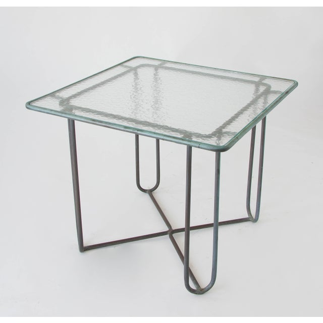 A small patio dining or card table in patinated bronze designed by Walter Lamb and produced by Brown Jordan. The table has...