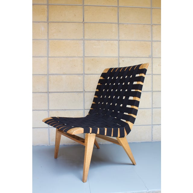 Rare and unusual, but undeniably sexy, this vintage, Mid-century chair is crafted from maple and strung with black webbing...