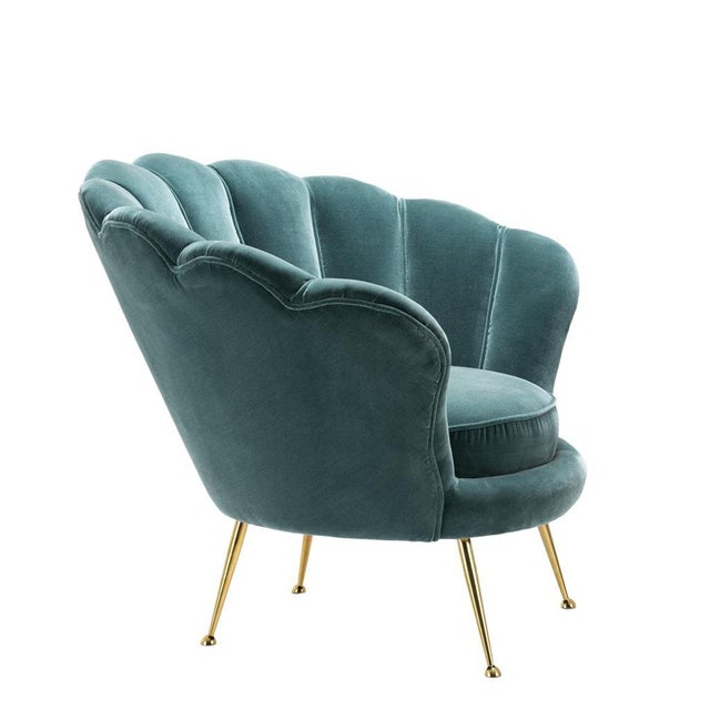 This turquoise velvet chair from Eichholtz comes with fun sea shell shaped back and brass legs and can transform a room...