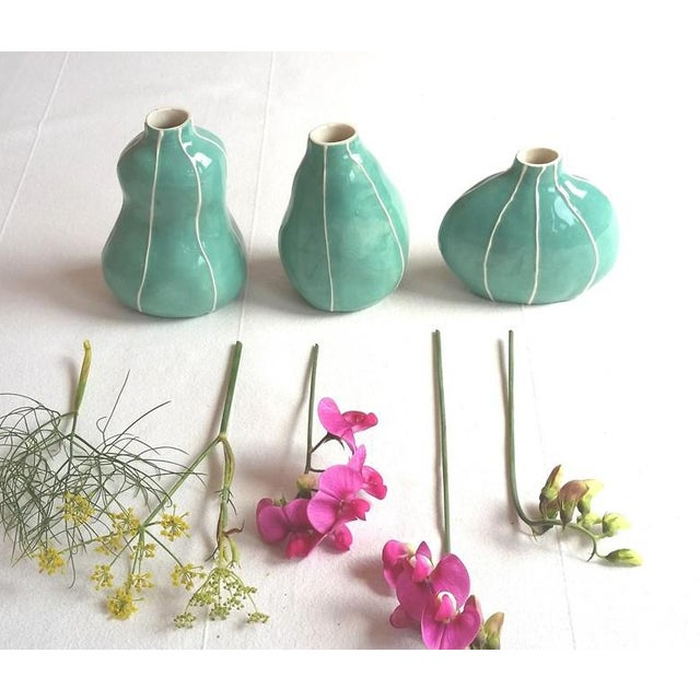 Three turquoise green bud vases in unique, handmade original shapes with thin, raised white stripes. This set has 3...