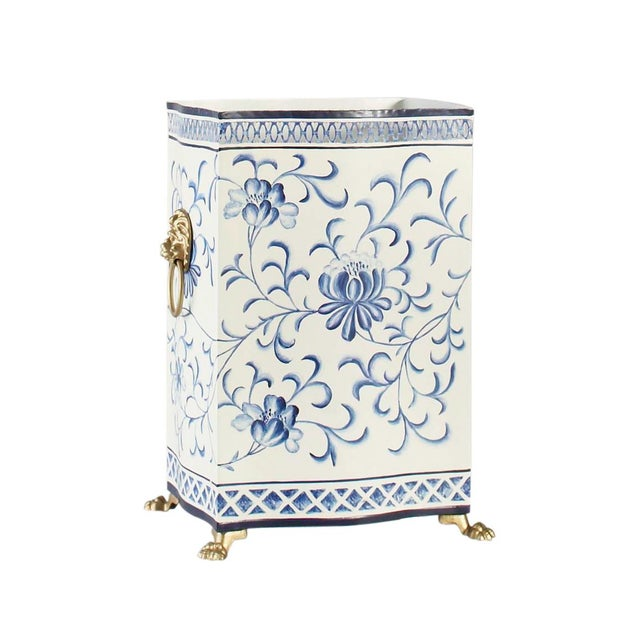 This is a blue and white wastebasket by Chelsea House Inc. The piece is hand painted on tole, featuring lion's head handles.