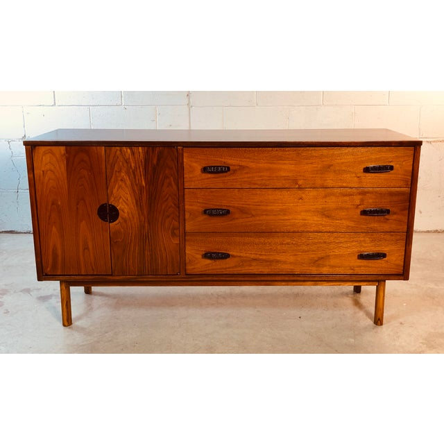 1960s walnut wood credenza by Bassett Furniture Co. The credenza has three drawers for storage on one side and open...