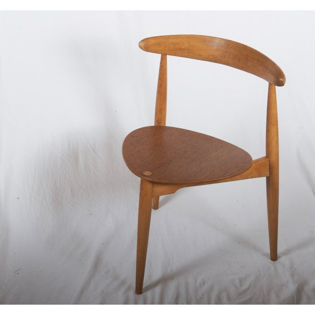 Hans J. Wegner stackable 'heart' tripod chairs, the seat made of the veneered teak frame and top rail of oak. Designed in...