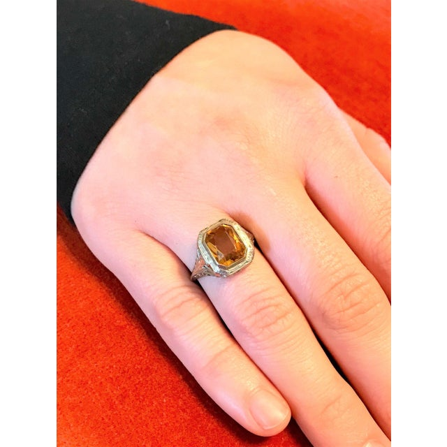 Circa 1910/20s 18k white gold filigree design ring bezel set with an emerald cut citrine gem. The ring is a size 7 and...