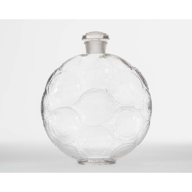 French Art Deco disk-shaped glass perfume bottle (RELIEF by FORVIL) with a design of repeating raised spirals and a...