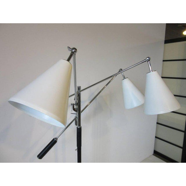 A three arm Triennale floor lamp with satin white cone shaped shades, chrome adjustable stems and staff with black leather...
