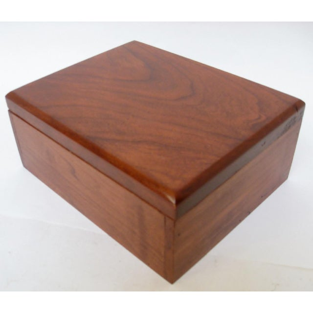 An unadorned cedar storage box finished in cherry stain, with flush seams and a heavy lift-off lid. Unlined interior. No...