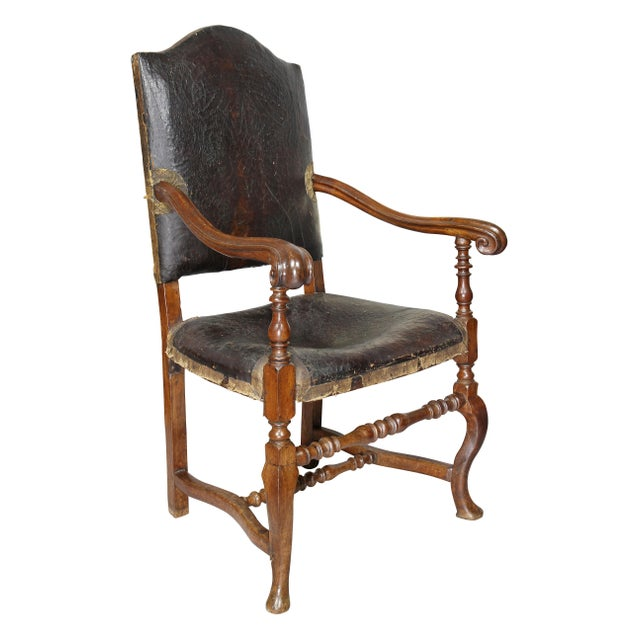 Each with an arched back with original leather, one chair the leather is distressed, carved arms and leather seats raised...