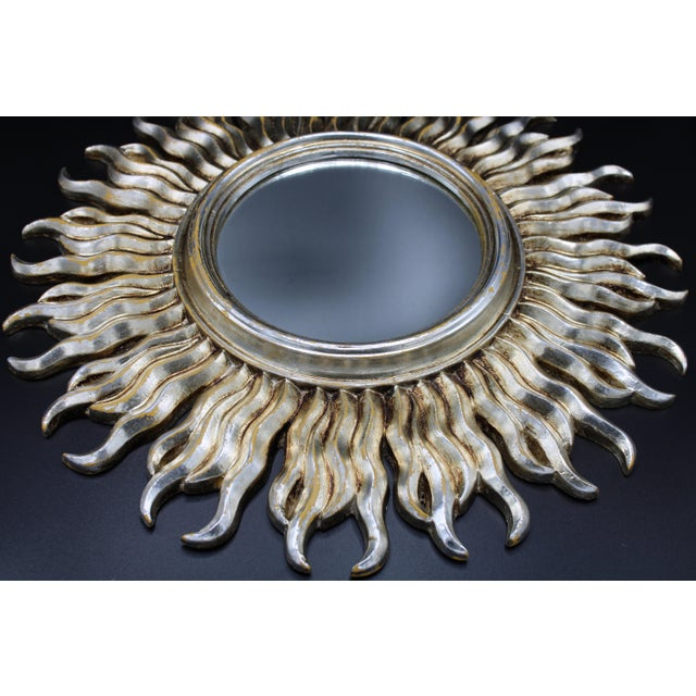 A stunning Mid-20th Century Italian resin sunburst mirror with wavy rays. The color is silver with gold undertones. Made...