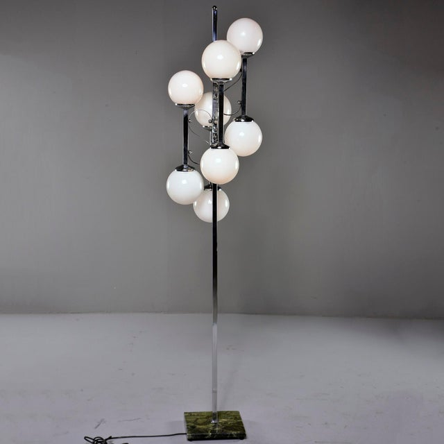 Circa 1970s Italian floor lamp has a green marble base with polished chrome center support with four arms and eight white...