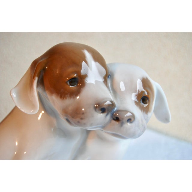 Lovely dog figurine of two pointer puppies in white, brown and grey colored porcelain. Marked with the Royal Copenhagen...