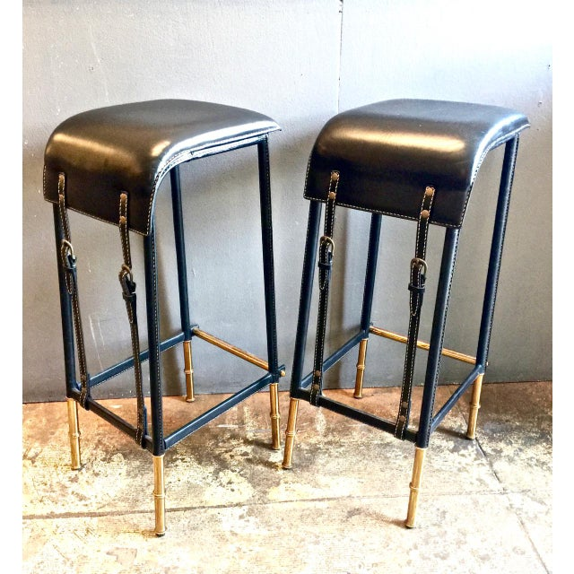 This is a superb pair of sexy Jacques Adnet bar stools that date to the 1950s. The Fine leather seats are strapped to the...