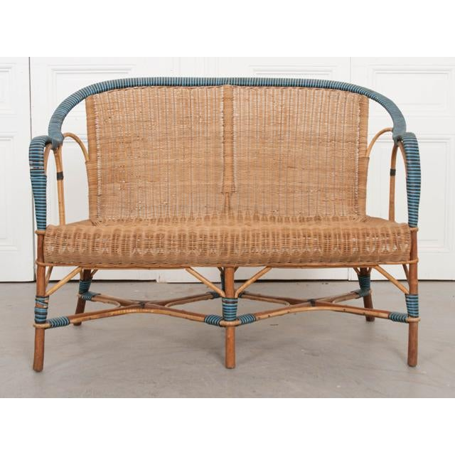 This fantastic vintage French woven-rattan settee, c. 1930's, accented with blue-and-black caning, would add a timeless...