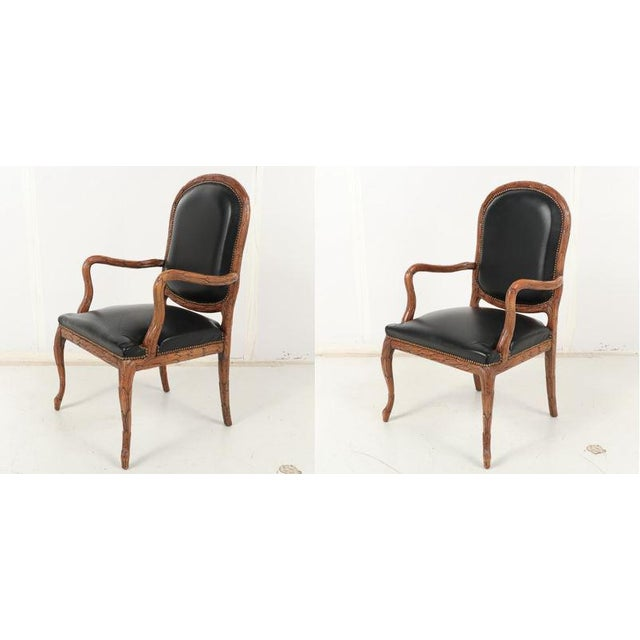 A Pair of Vintage Hand-Carved Italian Wood Leather Bound Armchairs. Black leather upholstery with brass button fastening....