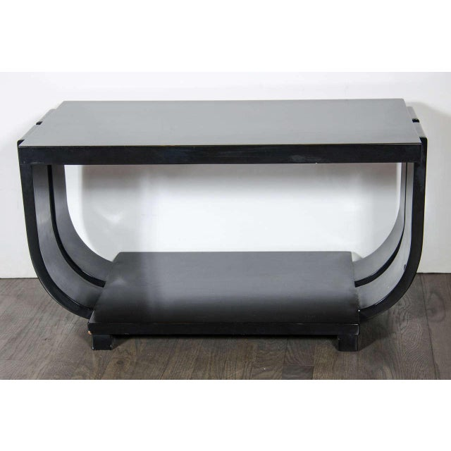 Machine Age cocktail table in a black lacquered finish, it has stylized double banded curved sides with a lower tier, and...