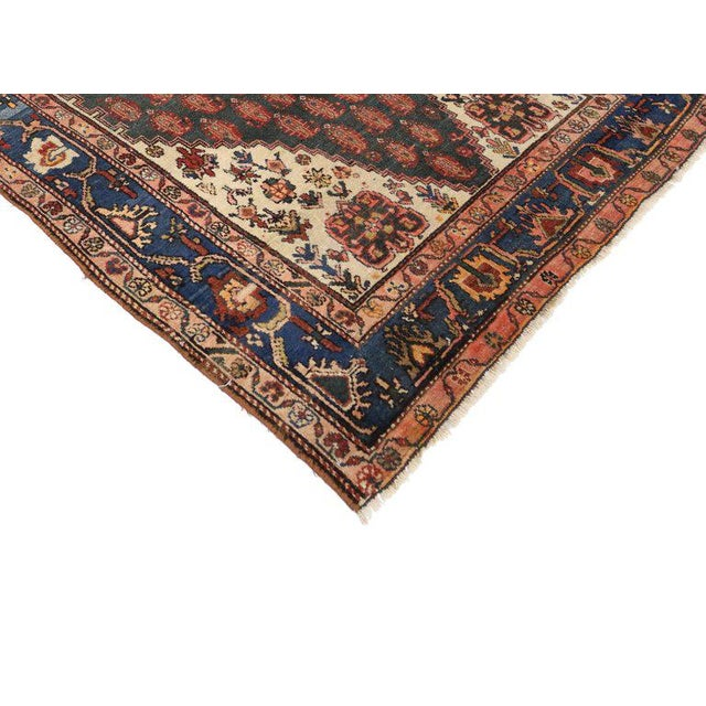 Modest yet full of character, this antique Persian Malayer rug features a modern traditional style displays an all-over...