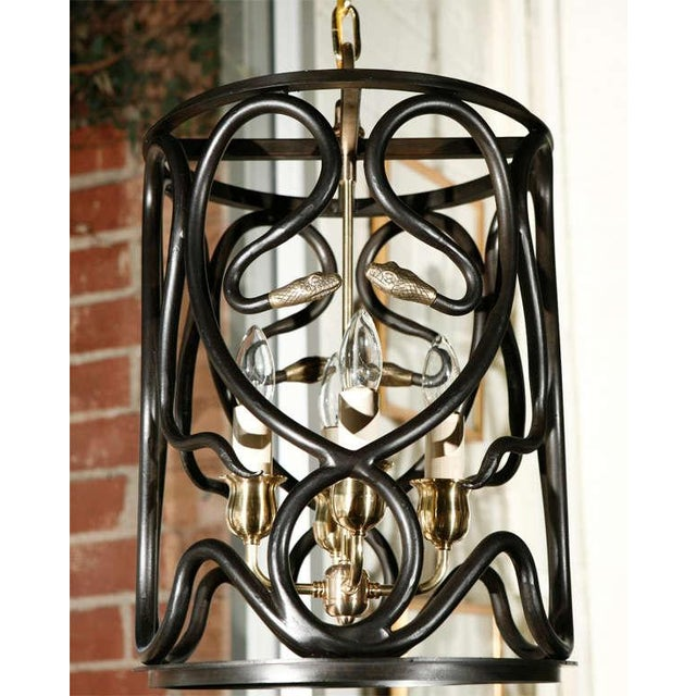 Paul Marra Snake Lantern Pendant in steel and brass. Finish: Steel with bronze patina, brass snake heads, rods and lamp...