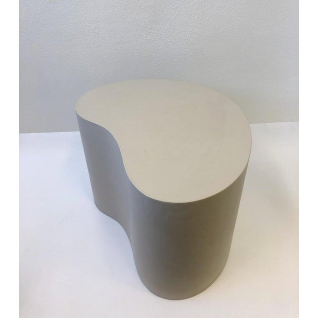 A kidney shape side table covered with off white leather designer by Karl Springer in 1985. The table is signed and dated....
