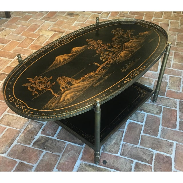 Oval metal Chinoiserie cocktail table in black and gold with brass frame and mounts. Scene on features a fisherman...