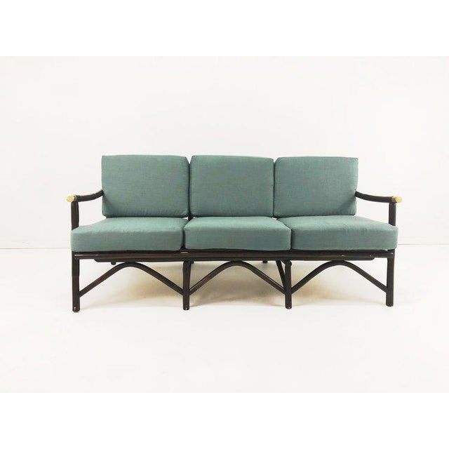 Dark wood bamboo sofa after Ficks Reed with brass end caps. Newly upholstered cushions in a beautiful blue fabric. Bamboo...