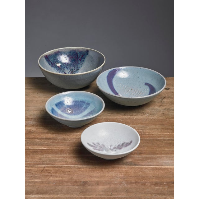 A set of four ceramic bowls with a rough glaze finish in blue tones, by Rolf Palm. The pieces are signed by Palm with the...