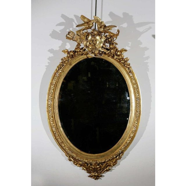 A delightful and entertaining French wall mirror in an ovular form cresting with a quiver of arrows amidst flora and...