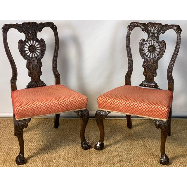 A fine pair of mid-19th century English elaborately carved Chippendale style mahogany side chairs upholstered in a coral...