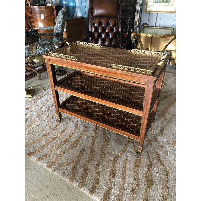 An unusually elegant mixed wood inlay bar cart having gorgeous criss cross design on each of the 3 tiers as well as rich...