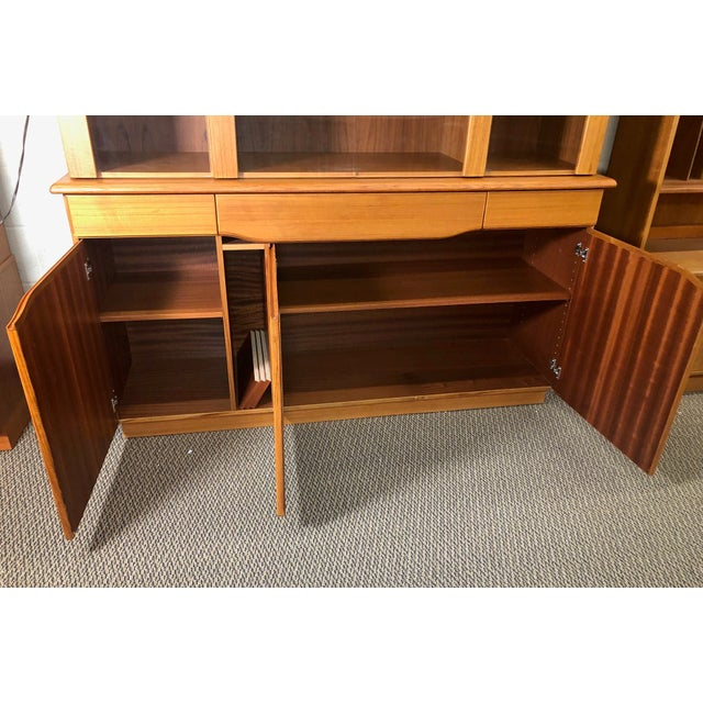 Beautiful teak china cabinet with hutch. The top and bottom are detached. Featuring glass shelves in the top section and...