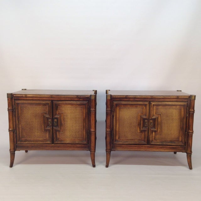 A pair of faux bamboo nightstands with stylish turned feet and timeless brass hardware. The cabinets have two cabinet...
