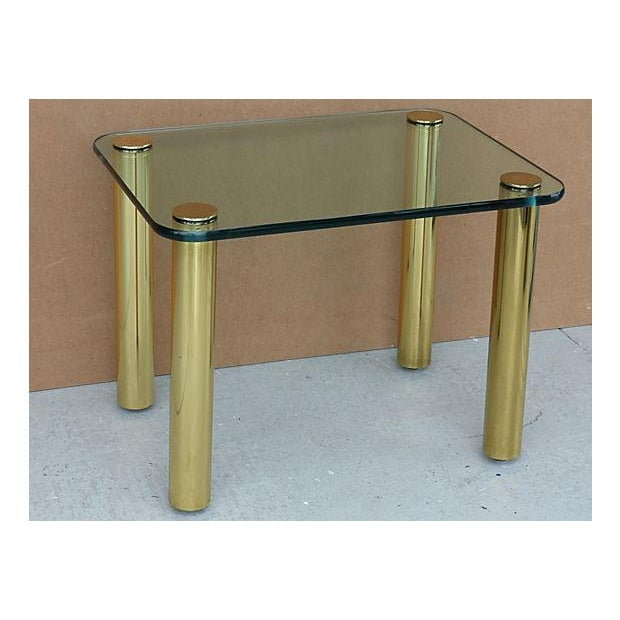 Stylish side from Pace Collection, unmarked. Features brass-plated heavy metal legs with adjustable footing and a tinted...