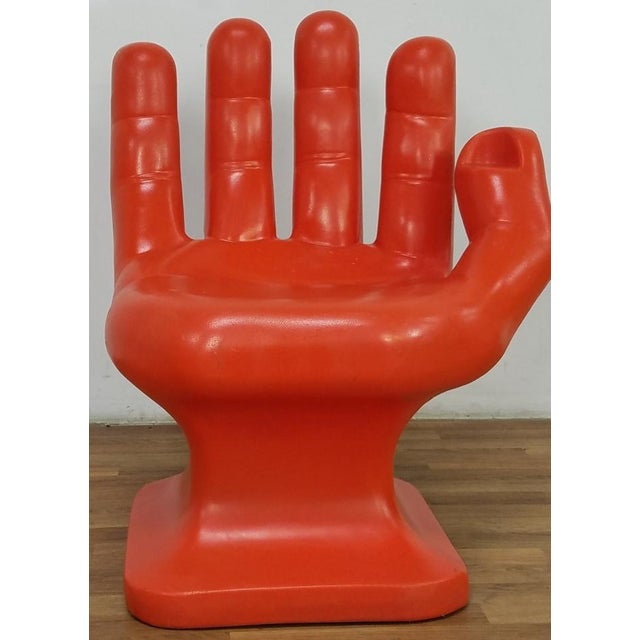 A Mid Century Modern sculptural hand chair, marked RMIC, molded as one piece in a red orange colored plastic. The four...