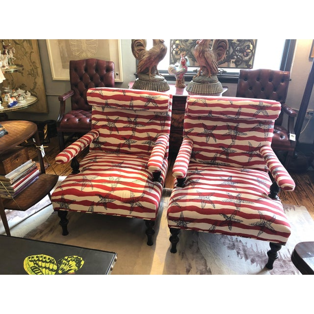 A big bold pair of designer custom club chairs upholstered in fun red white and blue striped fabric with starfish and...