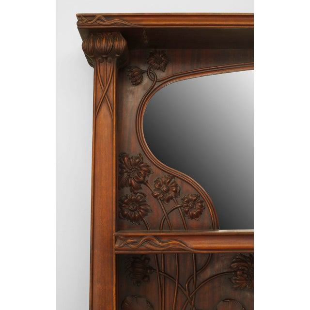 French Art Nouveau mahogany fireplace mantel with carved whiplash, lily pad & floral design with a shelf & shaped beveled...
