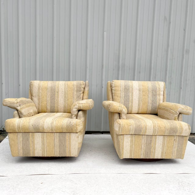 This striking pair of mid-century modern swivel lounge chairs feature iconic circular swivel bases in vintage walnut...